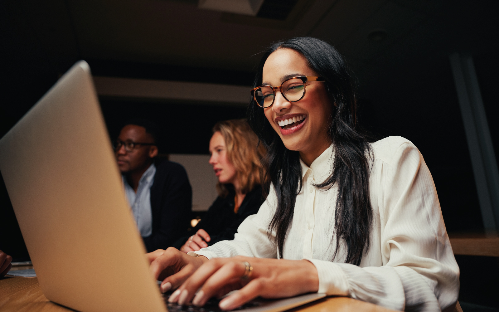 Girl with glasses smiling at laptop