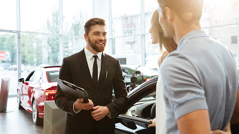 A salesman talking with a couple at a dealership