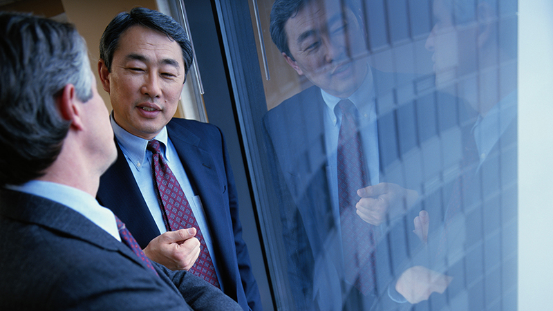 Two businessman talking near window