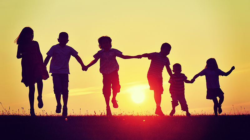 Silhouettes of six kids hand in hand towards a sunset