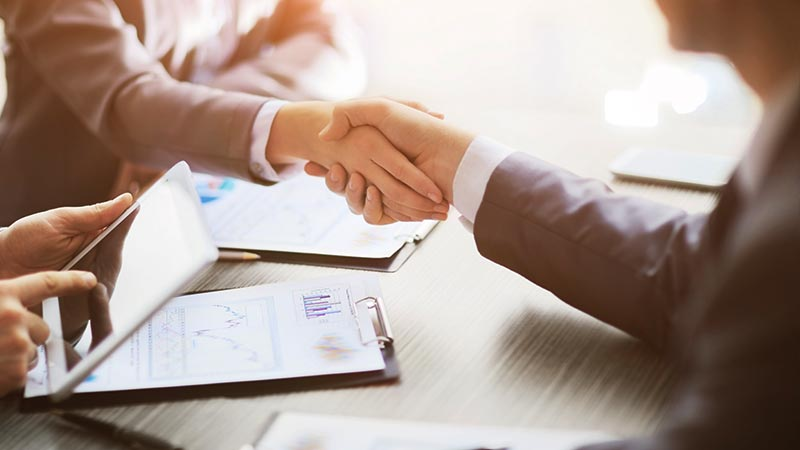 Business people shaking hands at table