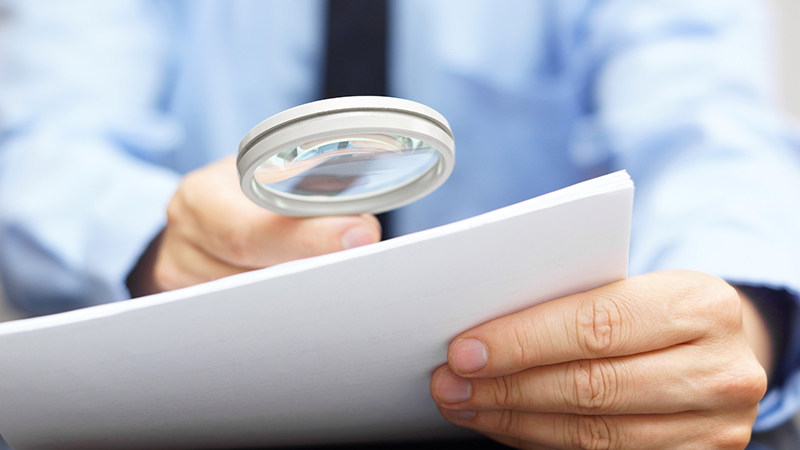 Hand holding magnifying glass over document