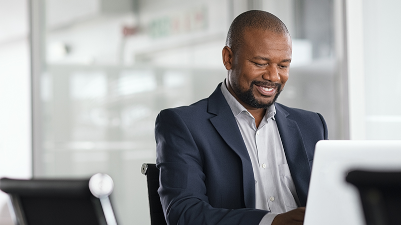 Smiling businessman working at computer