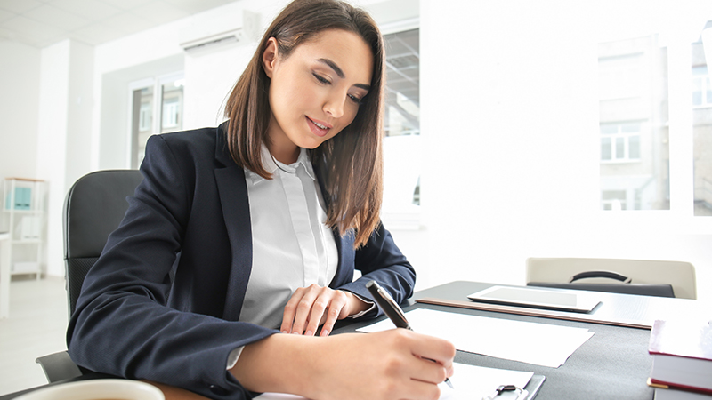 Businesswoman writing on documents at desk